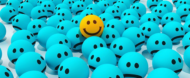 graphic of smiley face amidst group of unhappy faces
