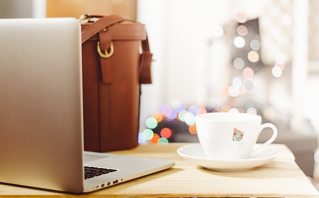Photo of desk with bag and laptop