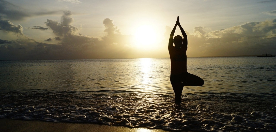 Photo: yoga at the beach with setting sun